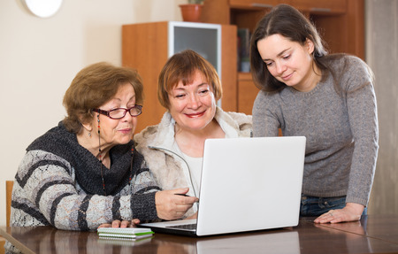 relative: adult pensioners and young relative making shopping list on laptop