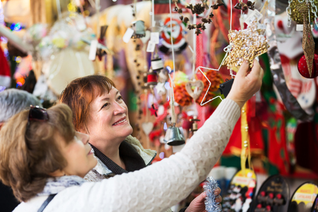 festal: Portrait of two elderly women choosing decorations at counter of Christmas market