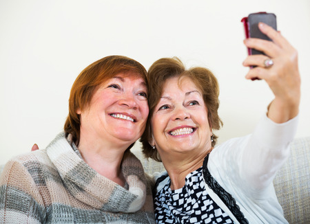 75s: Portrait of happy female pensioners making selfie on phone and smiling at home