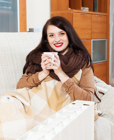 heat register: woman  with cup  near electric heater in home Stock Photo