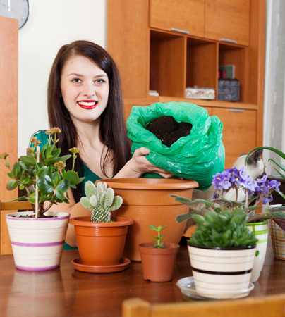 replant: Happy woman doing work in her small garden  at home