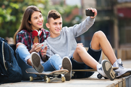 16s: Smiling boy and girl teens posing at mobile phone for selfie