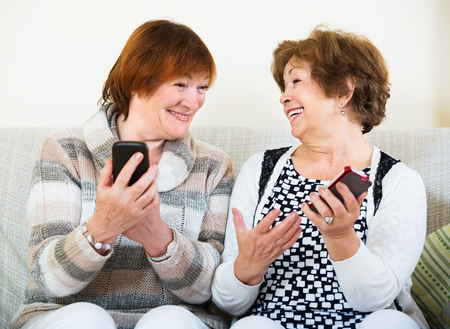 70 75: Smiling elderly women sitting with mobile phones in living room Stock Photo