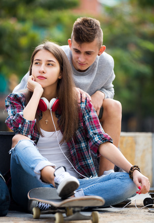 boy lady: Boy apologizes to her girl after an argument outdoor. Focus on the girl Stock Photo
