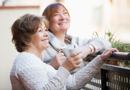 pullovers: Mature women in pullovers having cup of tea on terrace