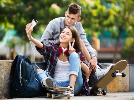 16s: Portrait of smiling boy and girl teens posing at mobile phone for selfie Stock Photo