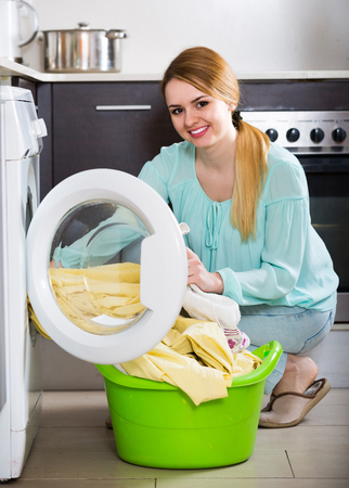 doing chores: Portrait of happy housewife with bed linen near washer Stock Photo