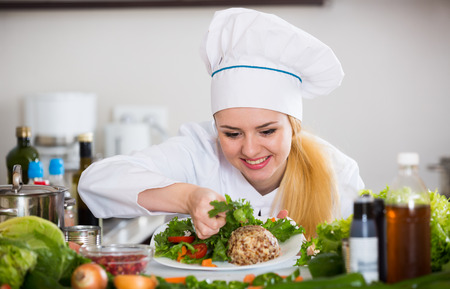 25 35: Professional chef decorating plate of salad with cheese and smiling Stock Photo