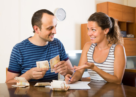 counting money: smiling american woman watching her husband counting money