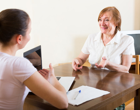 census: Smiling mature woman questionnaire for  young social worker