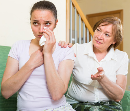 home comforts: worried mother comforts adult daughter   at home Stock Photo