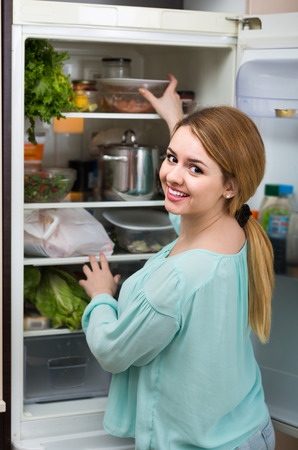 arranging: smiling  long-haired spanish woman arranging space in fridge at home