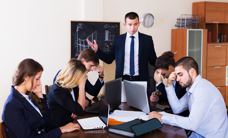 subordinate: Furious head of company and frightened subordinate officials in office. Focus on the right man Stock Photo