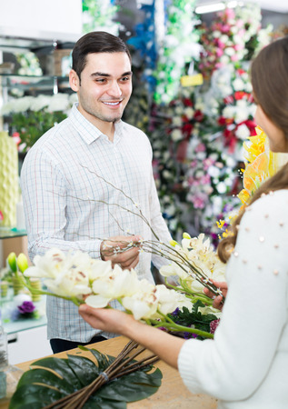 flower seller: Woman seller 30s  helping to pick floral bouquet of flowers man at flower shop
