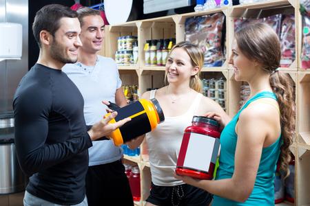 Vrolijke groep jonge volwassenen bespreken bodybuilding supplementen in de sportschool. Focus op de blonde vrouw