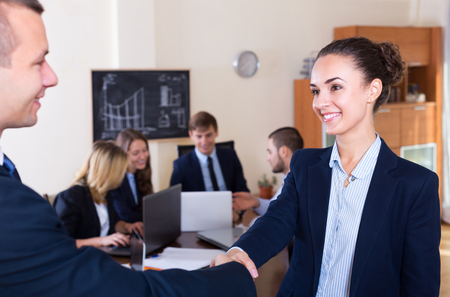 co operation: Firm handshake between two adult business partners at office meeting Stock Photo