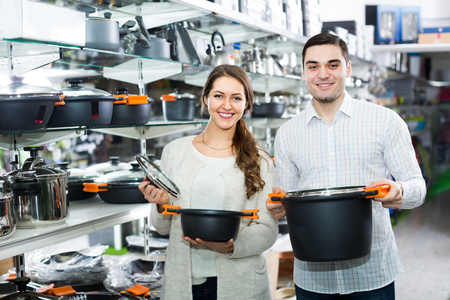25 35: Happy young couple choosing new pans for home kitchen in shop cookware Stock Photo