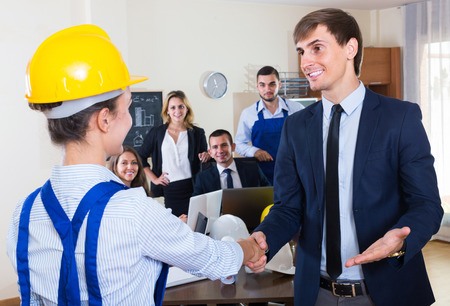 agency agreement: The head of architecture bureau and main specialist handshaking indoors Stock Photo