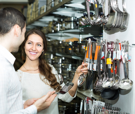25 35: Young european couple chooses cooking utensils at shop