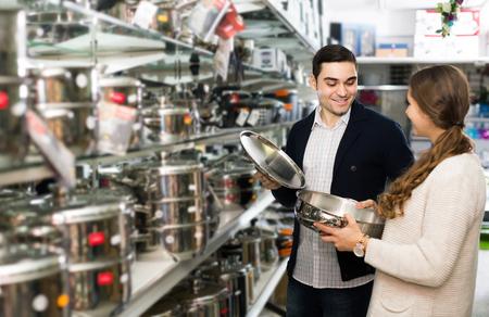 utensilios de cocina: pareja de adultos americanos positiva elige sartenes en la tienda de utensilios de cocina. centrarse en el hombre Foto de archivo