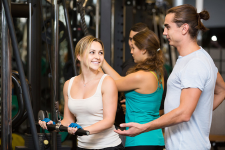 25 35: happy russian adults having strength training under coach control in gym