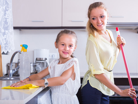 cleanup: Cheerful smiling little girl helping happy mother doing cleanup at kitchen Stock Photo