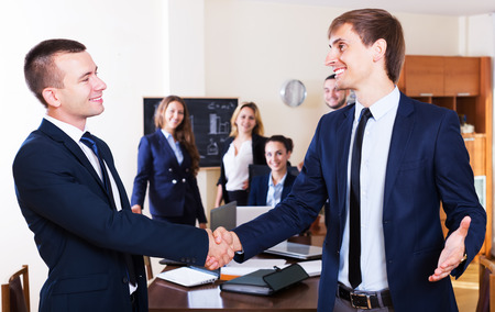warmly: The head of company warmly greeting new team member in office. Focus on the right man Stock Photo