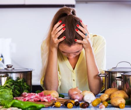 Vermoeide huisvrouw met vlees en groenten op de keukentafel