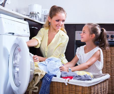 wash machine: Young housewife and little girl doing laundry together Stock Photo