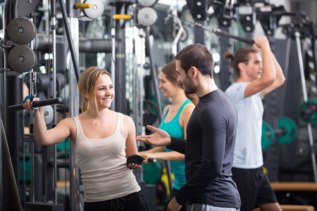 anaerobic: Happy young adults doing powerlifting on machines in modern fitness club Stock Photo