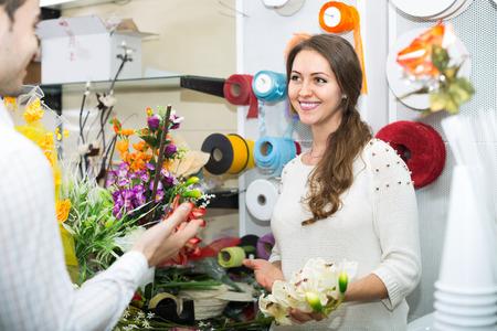 25 35: smiling european woman seller offering flowers man