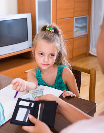 Allowance of pocket money: little girl and mother with purse