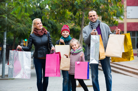 30 35: Happy smiling parents with school age children enjoying shopping tour Stock Photo