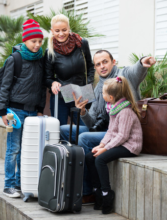 middle class: Happy middle class family of four checking direction in city map outdoor