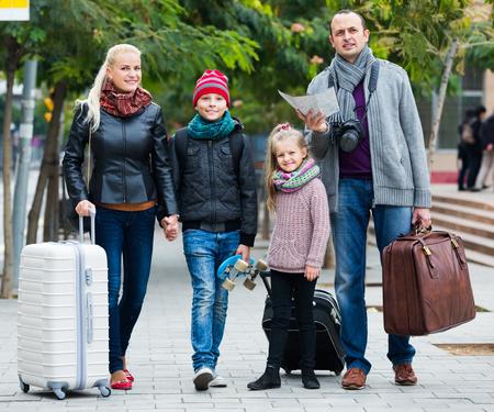 middle class: familia de clase media de cuatro miembros feliz comprobar una dirección en el mapa de la ciudad