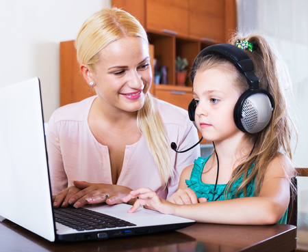 mum and child: Smiling nanny and girl with headset playing computer game at home