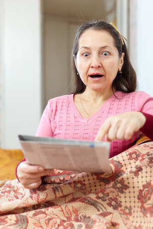 chagrin: fright and amazed  woman with newspaper at home Stock Photo