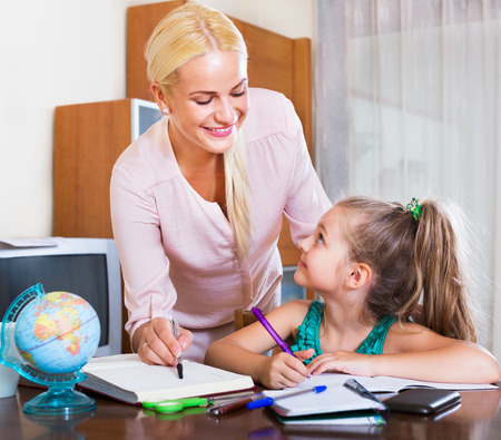 clothes interesting: Portrait of happy adult woman and her child having a lesson indoors Stock Photo