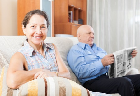 gladful: Portrait of smiling elderly couple on the couch with the newspaper in home interior