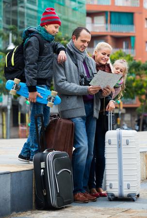 clase media: familia de clase media de cuatro miembros feliz el control de la dirección en el mapa de la ciudad Foto de archivo