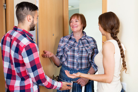daughter in law: Happy couple greeting elderly mother at home Stock Photo