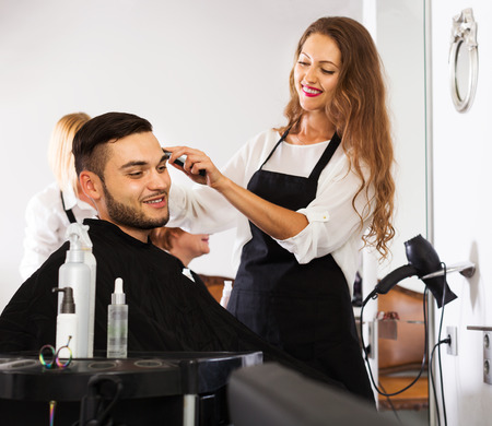 25 35: Barber makes the haircut for man in the barbershop