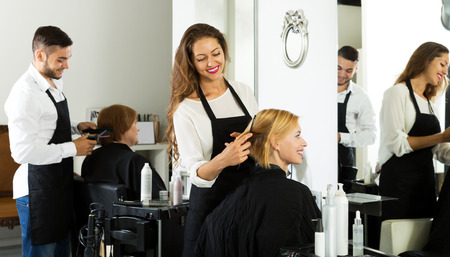25 35: Hair stylist working on haircut for positive girl