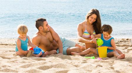 Gelukkige ouders met kinderen spelen met zand op het strand Stockfoto