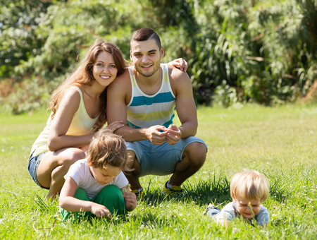 3 4 years: Happy smiling young family of four resting in sunny summer park