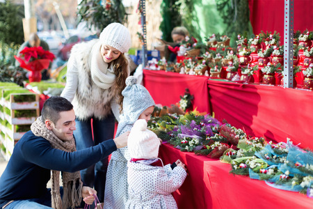 25 30 years women: Happy married couple with two children choosing Christmas star flower at market.