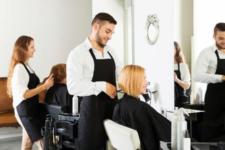 peluquería: Peluquero corta el pelo de la chica joven en el salón de belleza