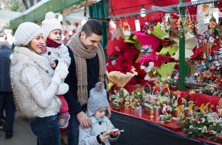 25 30 years women: Young parents with little girls at counter with Poinsettia. Focus on woman