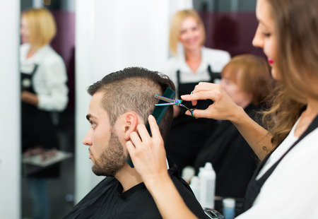 25 35: Professional woman hairdresser doing hairstyle for young men Stock Photo