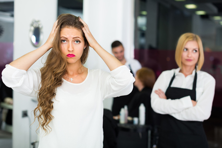 25 35: Portrait of discontented longhaired female at the hairdressing salon